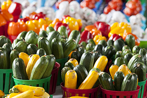 Photo of summer squash in baskets and fresh bell peppers at at farm market.
